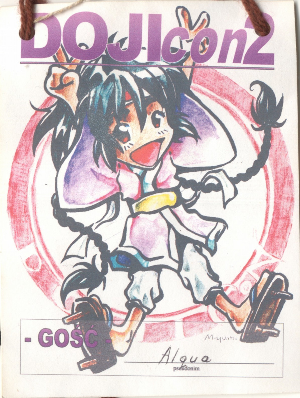 A convention badge with a happy manga style character in the middle. On top there is a name of the convention: DOJIcon 2.
