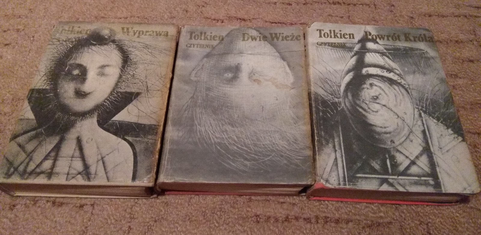 Three book with weird pictures on them. Left to right - a character which hair looks slightly plant like, an upside down head and a faceless character in a wizard hat. All pictures are black and white.