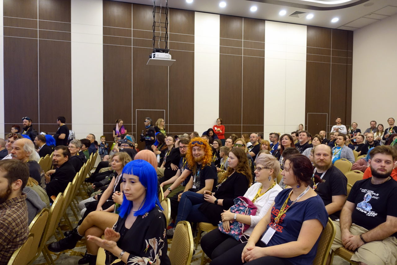 Many people sitting on chairs in a big room.