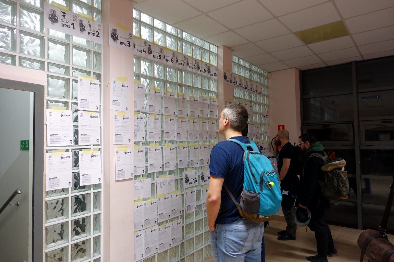 Three man looking at lists posted to the glass wall.