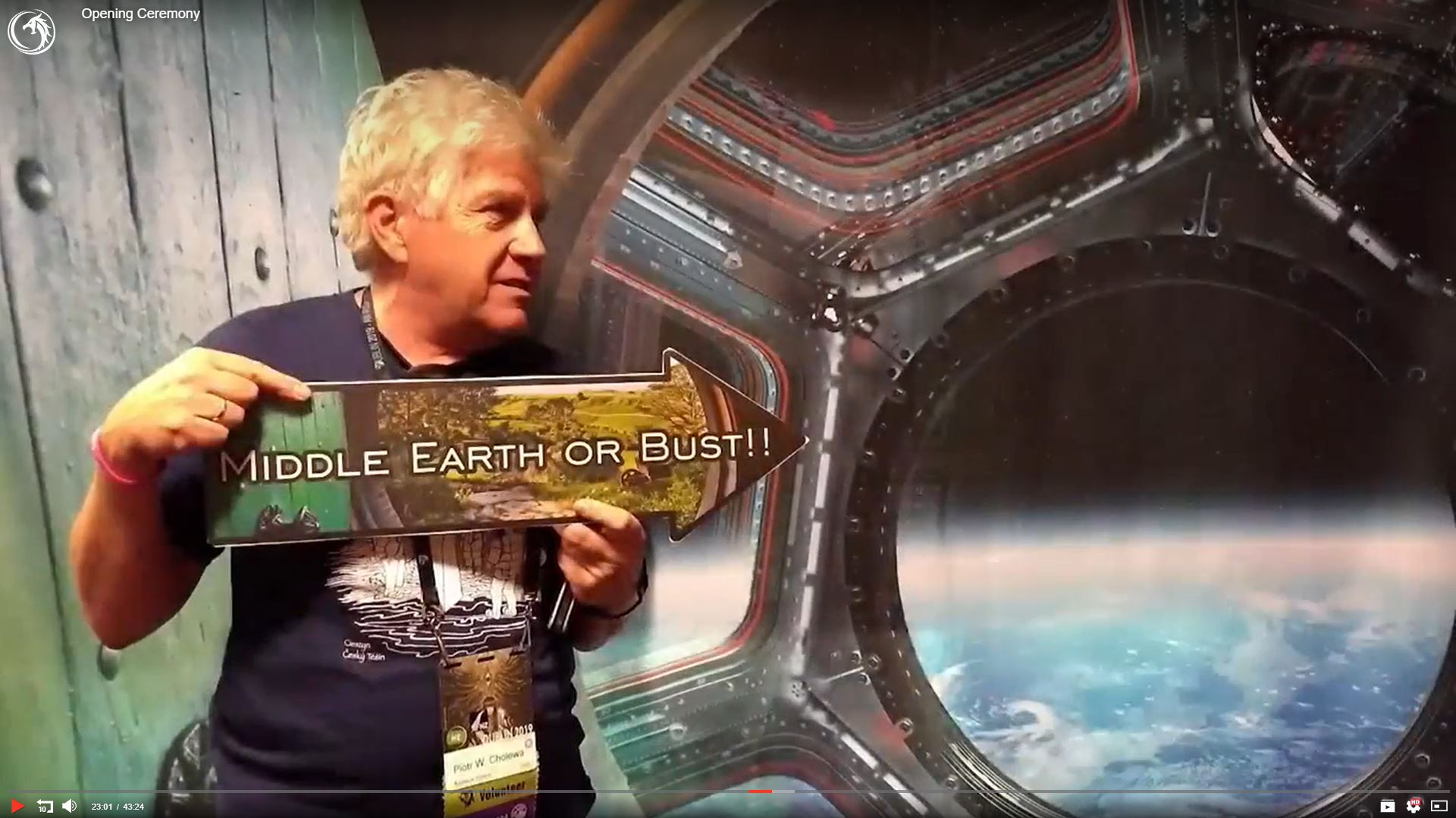 Man posing to the picture with 'Middle Earth or Bust!!' sign. Behind him there is a background with open hobbit door and a view from a spaceship window.