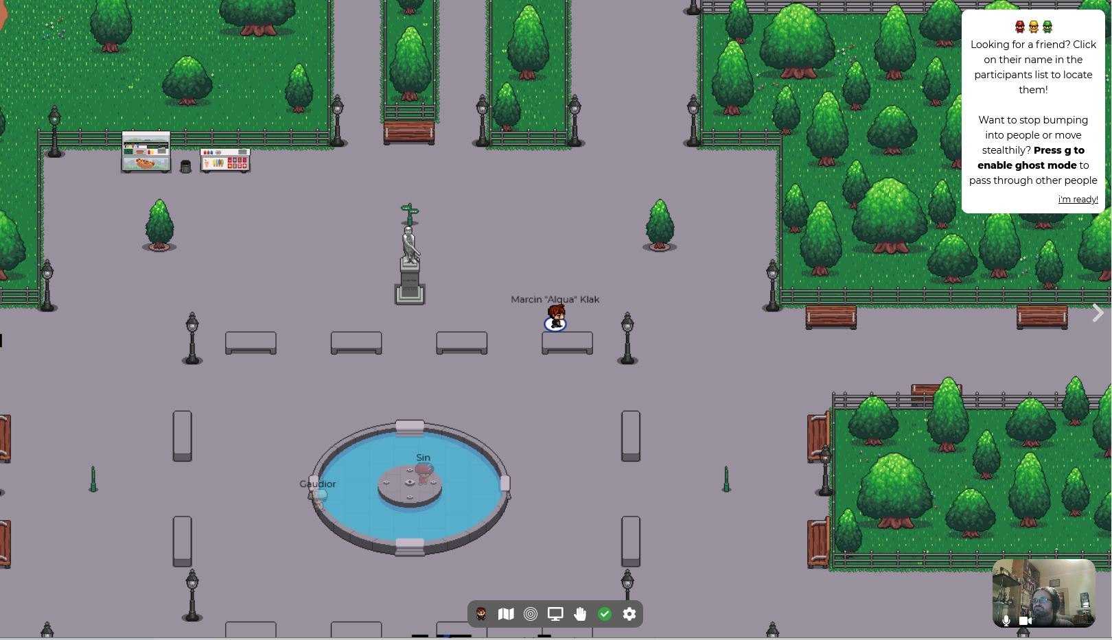 Screen from a simple game. There is a fountain in the center surrounded by benches. There is a small animated human figure near one of the benches. Top and right side of the picture are covered with trees.