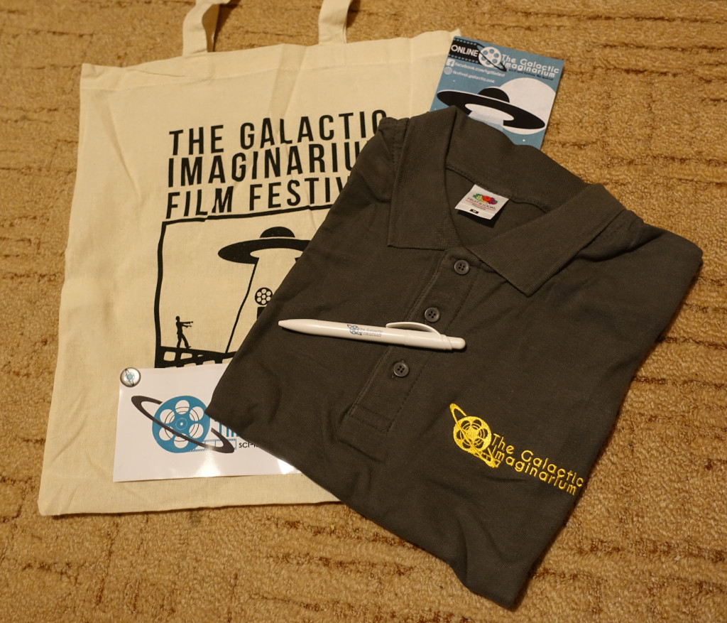 A pile of TGIFF materials. At the bottom there is a totte bag with convention logo. On top of it there is a polo shirt with emboidered logo and name. There are also two leaflets and a pen.