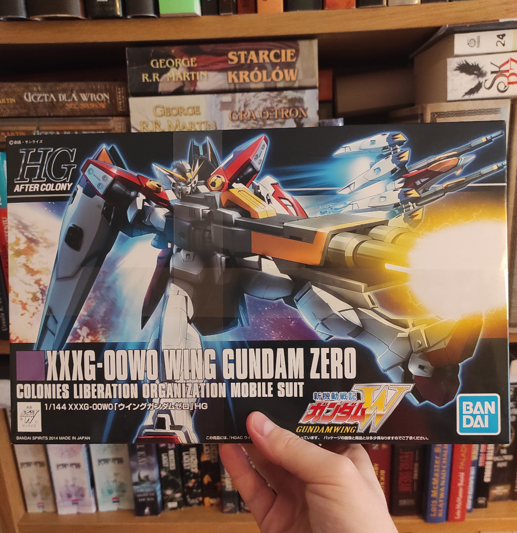 Picture shows a box in front of the book shelf. The box cover presents a robot with large gun.